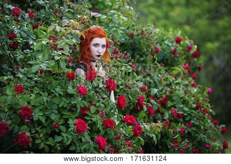 The red-haired girl posing on a background of a bush with red roses. Red lips and red nails. Ring on a finger. Long hair. Pale skin.