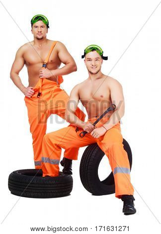 car mechanics with tools and tire, isolated against white background