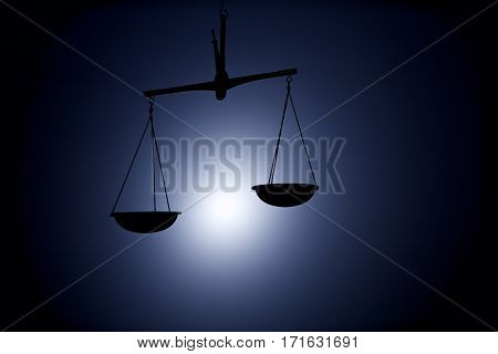 justice scale silhouette on dark blue background