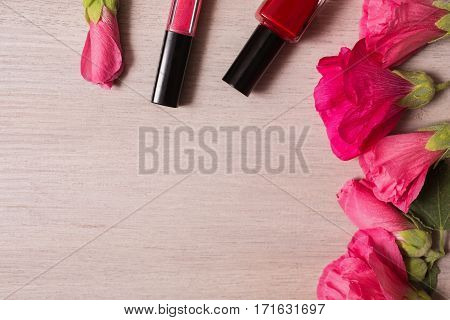 Red flowers lie on the wooden background. Space for text and design. Female nail polish and lip gloss. Natural cosmetic. Personal care