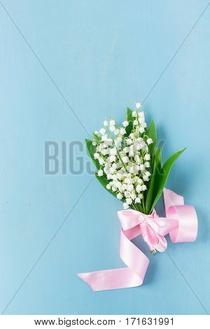 Bouquet of Lilly of the valley fresh flowers on blue wooden background with copy space
