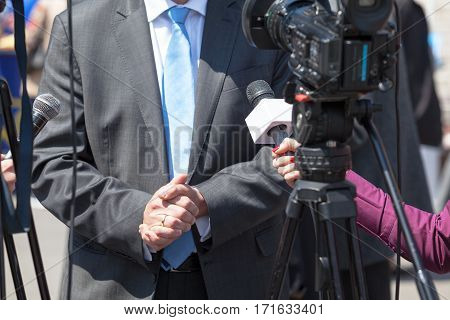 Famale reporter holding microphone conducting TV interview