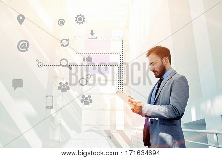 Smart businessman holding touch pad in modern office space with big copy space area. Young male coworker personalizing settings and multimedia application on his new tablet infographics effect