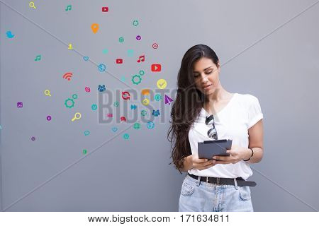 Charming latin woman holding her digital tablet computer while standing against background with popular application and multimedia icons. Female using contemporary touch pad with infographics effect
