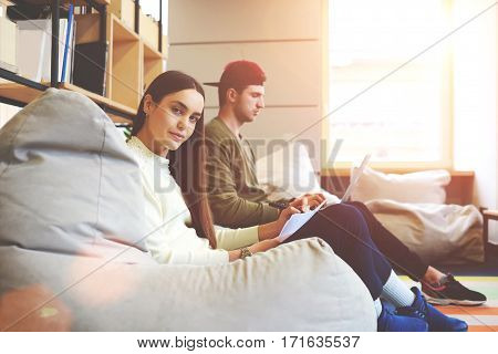 Two journalists are preparing articles and texts correcting the mistakes by the pen computer programs.Young couple studying together in coworking space sitting near window concentrated on their work