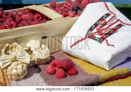 Raspberries in a basket on a bench with bast shoes