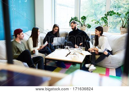 Yong freelance crew working hard on finding creative solution for internet social media tasks sitting in coworking space using modern technology and consulting with skilled professional leader