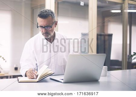 Successful mature entrepreneur working with new business project while is using laptop computer and notepad. Handsome businessman writing notes in notebook after analyzing monthly report on net-book