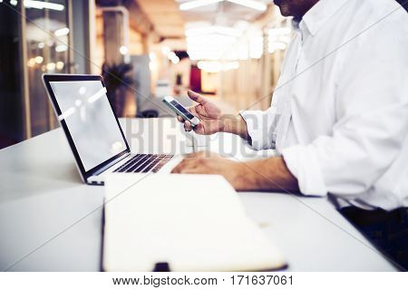 Skilled businessman synchronizes the mobile device to a portable laptop computer by using the application. Male freelancer sending e-mail on cell phone while standing in modern office interior
