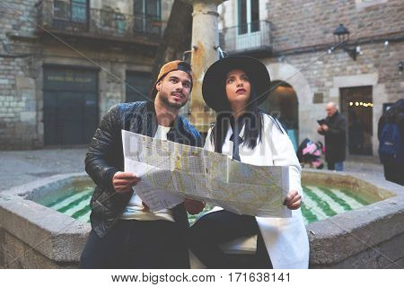 Spellbound tourists sitting on an old fountain in a small cozy patio in the historic part of the city. Young couple of travelers are crazy about the architecture of the old courts of Barcelona town