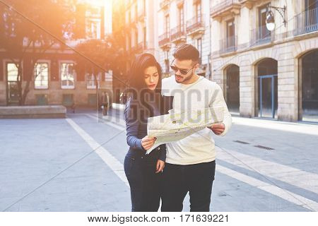 Fashionably dressed couple of travelers lost in the streets of the old town. The hot young guy and his beautiful brunette opened the map exploring it to continue their romantic walk on a spring city