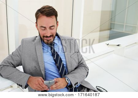 Smiling man entrepreneur is reading good news via mobile phone about his project while is sitting in office interior. Cheerful male proud CEO is using cellphone while waiting plane in airport hall