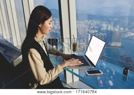 Businesswoman is keyboarding on portable laptop computer while sitting in interior with contemporary design near window with view of Honk Kong city.Young Asian female on net-book with startup project