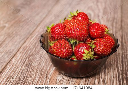 Red ripe strawberries in a transparent plate. Summer ripe berries