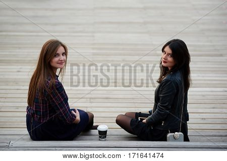 Two female student are posing while are sitting with take away coffee on a campus during break between lectures. Charming women are looking in camera while are enjoying recreation time outdoors