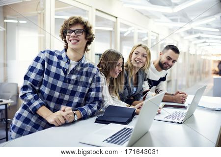 Crew of male and female journalists having fun during working on publishing information on web pages in prime time using modern laptop computer and wireless connection to internet in newsroom workshop