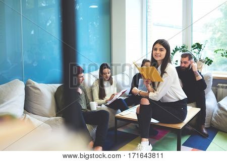 Group of talented male and female international students working together on coursework project planning strategy of report and reading manual textbooks on marketing researches sitting in coworking space
