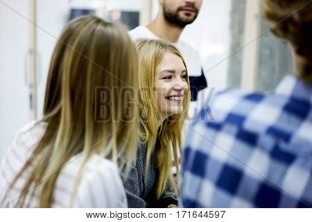 Portrait of young female international student on blurred frontage enjoying leisure time while having friendly conversation with male and female classmates during break sitting in modern library
