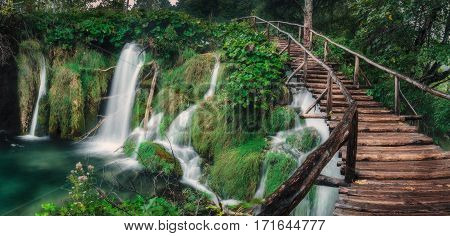 Waterfall in the lush green forest with long wooden stairway.