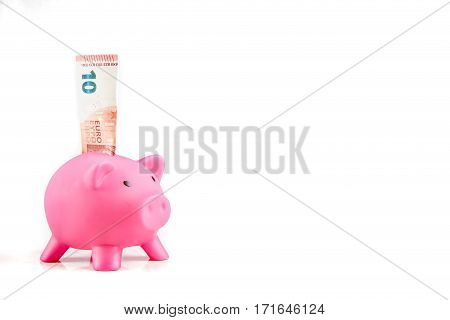 Piggybank with ten Euro banknote with copy space