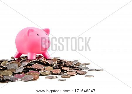 Piggybank standing on pile of coins with copy space