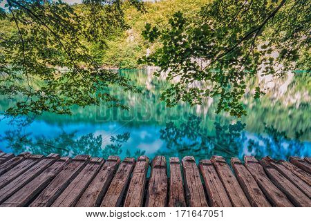 Wood bridge with low hanging trees over blue and gree Plitvice lakes,Croatia.