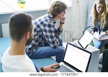 Male and female students discussing ideas for new business startup monitoring latest news using laptop computer with blank display connected to fast 5G wireless while spending time in office indoor