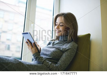 Charming young well-dressed woman making online banking paying for purchases in web store making operations via modern touchpad connected to free wireless internet sitting near big window in cafe