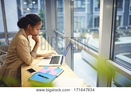 Professional administrative manager making annual report of job comparing information from database on laptop computer connected to free wireless connection in free wifi zone indoor during working day
