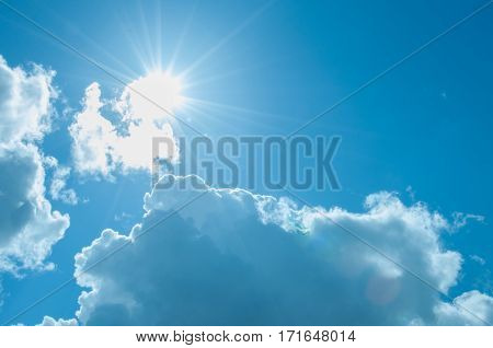 Sunshine appearing through the cumulus clouds on a sunny day.