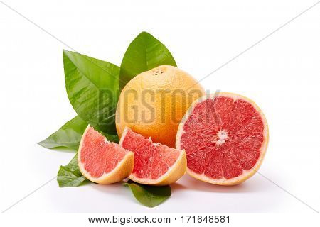 Fresh juicy whole grapefruit with green leaves and appetizing slices of  ripe grapefruit on a white background.