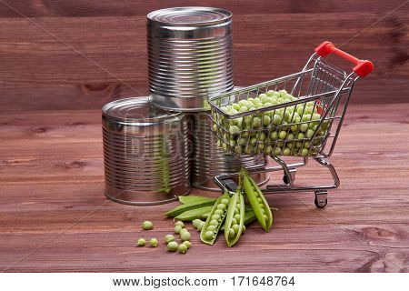 Shopping trolley with fresh green peas, cans with canned peas and  ripe pea pods on a wooden table.