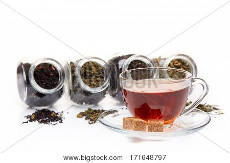 Various kinds of dry tea in glass jars and cup of aromatic tea standing on a white background.  Different kinds of tea leaves.