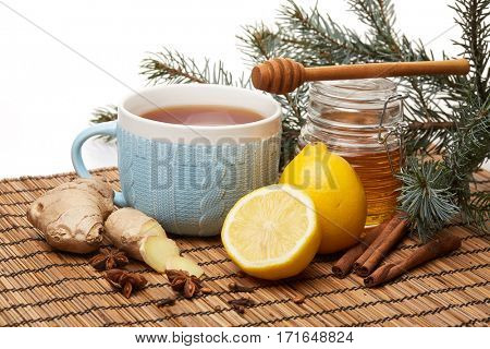 Honey in glass pot  and blue cup of tea with ginger, cinnamon, anise and lemon standing on bamboo mat on a white background.