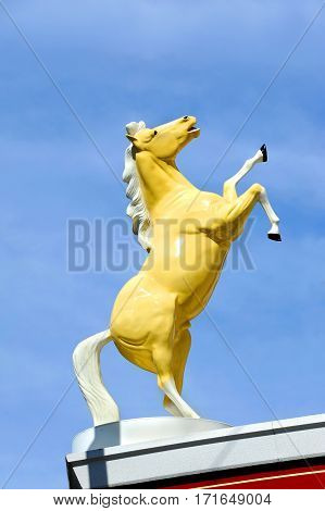 Statue of a wild stallion rearing its legs into the air is sillouetted against a blue sky in Montana. Wild west symbol.