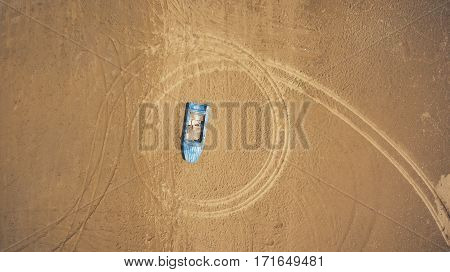 Top view aerial photo from flying drone of a blue boat on a beach in Thailand in sunny summer day. One wherry is lying on a sand with copy space for your travel blog