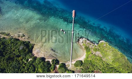 Top view aerial photo from airplane of a island nature landscape with tropical plants near sea with calm waves and jetty. Wonderful scenery with Indian ocean. Beautiful Mediterranean seashore