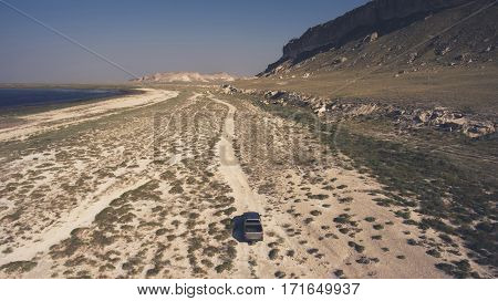 Aerial photo from drone of riding pickup car in Texas area near mountains. Wonderful trip to Asia with rental machine. Beautiful wild nature landscape for travel website. Concept of freedom in journey