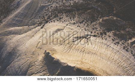 Top view aerial photo from drone of canyon range in arid wilderness landscape. Flight over American National Park with rock mountain in desert valley. Beautiful nature background for travel website