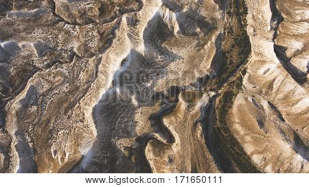 Top view aerial photo from flying drone of a beautiful arid rocky mountains in Kazakhstan National Park during evening twilight. Amazing nature landscape as perfect background for travel website