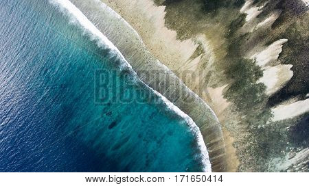 Top view aerial photo from flying drone of a wonderful nature landscape with sandy beach with beautiful coral bottom for snorkeling. Indian Ocean seascape with beautiful calm waves.Website background