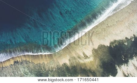 Top view aerial photo from flying drone of a beautiful sea scenery with coral bottom and sandy beach with copy space area for your text. Wonderful nature background of Indian Ocean landscape