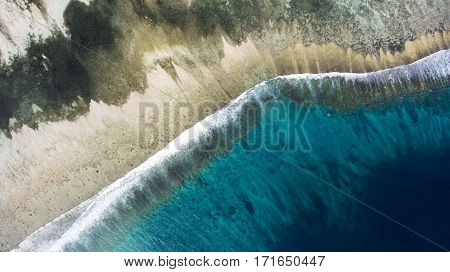 Top view aerial photo from flying drone of a wonderful nature landscape of Indian Ocean with coral bottom perfect place for snorkeling with masks. Beautiful seascape with calm waves with copy space
