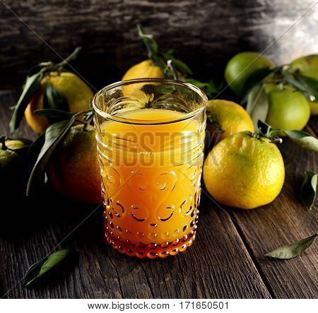 Glass of fresh tangerine juice with ripe tangerines, leaves and old-fashioned straw on a wooden background