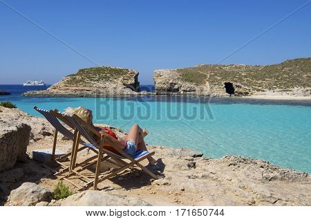 One alone woman relaxing in Comino island, Malta with the view to emerald sea. Paradise in Malta. Visit Malta. Caucasian white woman relaxing in the beach