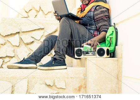 Young indian man with pc laptop listening music at radio cassette player on white urban background - Freelance guy using modern and old technology - Soft vintage filter look focus on tape recorder