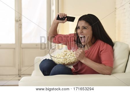 young happy attractive woman alone at home sofa couch watching excited television football sport match or TV contest eating popcorn cheering crazy fan celebrating victory or goal
