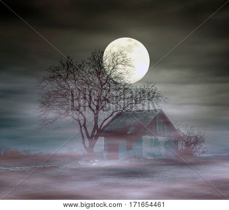 Spooky ghost house and full moon at foggy night
