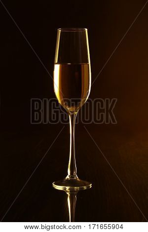Glasses with white wine on black mirror table. Celebrities composition