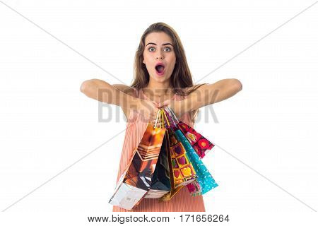 girl with great surprise keeps itself in the hands of the packages is isolated on a white